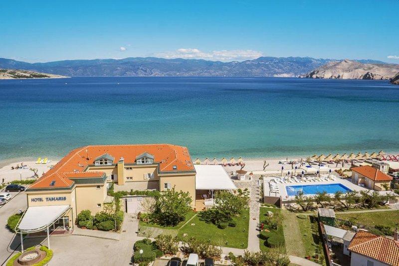 Situato a Baška, sull'Isola di Krk, l'Hotel Tamaris gode di una posizione fronte mare e offre sistemazioni dotate di aria condizionata e Wi-Fi gratuito, e una spiaggia attrezzata con lettini e strutture per lo svago.